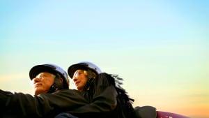 Ein Paar fährt mit Helm und Brille Motorrad