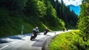 Motorradfahrer auf einer Straße durch einen Wald
