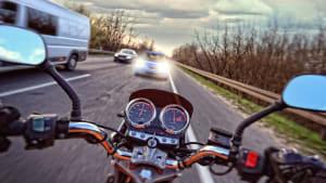 Ein Autofahrer steuert bei einem Überholvorgang direkt auf einen Motorradfahrer zu