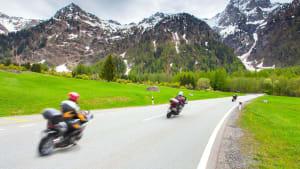 Drei Motorradfahrer auf einer Straße in den Alpen