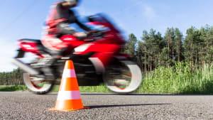 Fahrer auf rotem Motorrad bei Fahrübungen mit einer Pylone