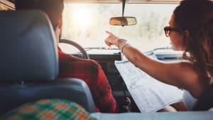 Frau weißt Mann Weg mit Landkarte im Auto