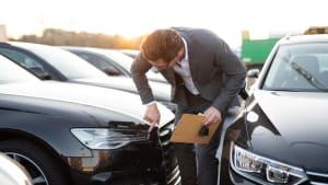 Ein Autoverkäufer prüft den Neuwagen vor Verkauf auf Lackschäden