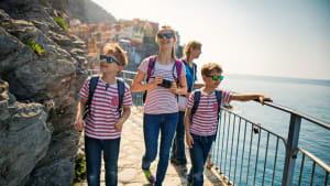 Familie bei einer Wanderung. Im Hintergrund die bunten Häuser der Cinque Terre
