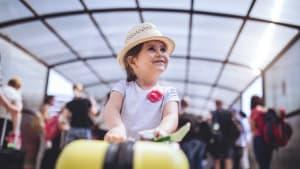 Ein Kind steht mit einem Koffer in einer Wartehalle