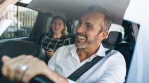 Ein Mann fährt Auto und lacht.