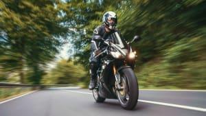 Ein Motorradfahrer, fährt auf einer Landstrasse mit seinem Motorrad.