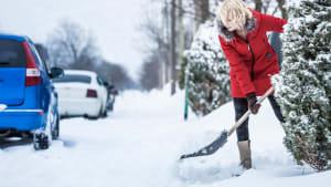 Frau nräumt Schnee vor Ihrem Wohnhaus