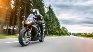 Motorradfahrer in schwarzer Lederkleidung fährt auf einer Landstraße am Waldrand