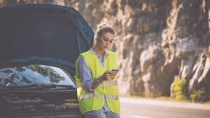 Frau ruft mit ihrem Handy nach Autopanne um Hilfe