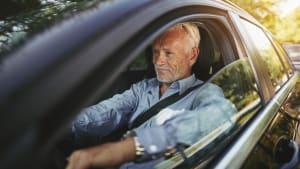 Senior sitzt hinter Steuer im Auto
