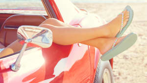 Frau mit Flip Flops lässt Füße aus dem Auto hängen