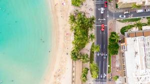 Drohnen Bild von einer Küstenstrasse auf Hawaii, mit Meer, Palmen, Straße und Häusern.