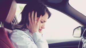 Frau hat Stress im Auto und hält sich die Ohren zu