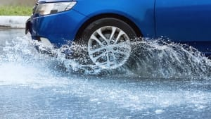 Ein Auto fährt durch eine tiefe Pfütze und das Wasser spritzt.
