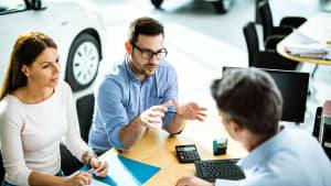 Paar verhandelt mit Autohändler über Autokauf
