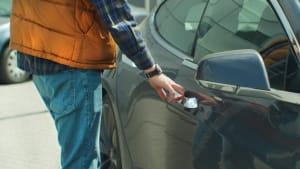 Mann öffnet eine Autotür