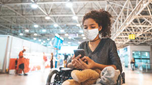 Junge Frau schaut an einem brasilianischen Flughafen auf ihr Handy