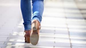 Frau läuft einen Gehweg entlang