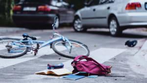 Unfallszene mit Fahrrad und Schulranzen und einem Auto