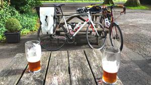 Zwei Biergläser stehen auf einem Tisch, im Hintergrund sind zwei Fahrräder zu sehen