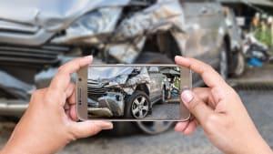 Frau fotografiert einen Unfallschaden am Auto