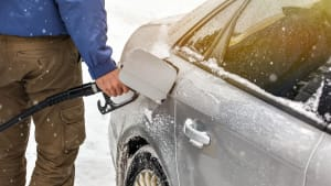 Mann tankt Auto im Winter