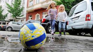 Zwei Mädchen laufen beim Spiel mit einem Ball über eine Straße