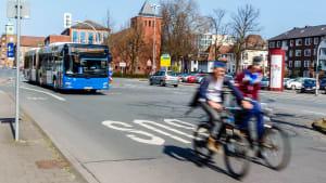 Ein Bus, Auto und zwei Fahrradfahrer auf einer Straße in Münster