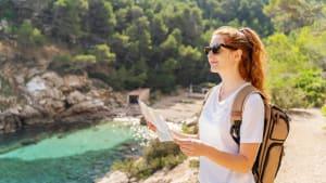 Rothaarige Frau mit Sonnenbrille wandert auf Ibiza oberhalb einer türkisen Bucht
