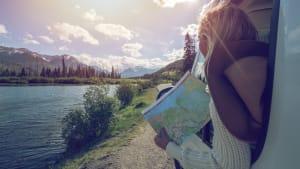 Eine Frau hat eine Landkarte in der Hand und lehnt sich aus einem Auto und schaut auf Berge und auf einen See.