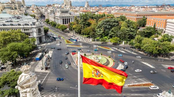 Spanische Flagge mit Plaza de Cibeles in Madrid im Hintergrund