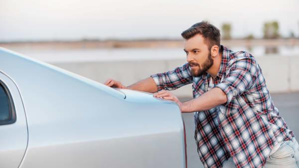 Junger Mann schiebt sein Auto nach einer Panne