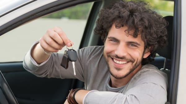 Mann sitzt im Auto mit Schlüssel in der Hand