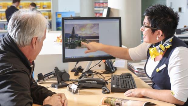 ADAC Reiseexpertin zeigt einem Kunden auf dem Bildschirm ein Reiseziel