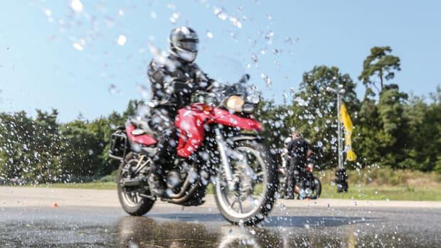 Rotes Motorrad fährt auf nasser Fahrbahn beim ADAC Fahrsicherheitstraining
