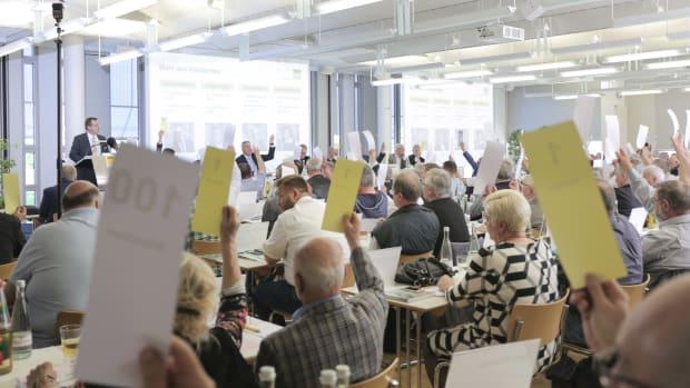 Mitglieder des ADAC Nordbaden sitzen im Saal und heben Wahlzettel für eine Abstimmung nach oben