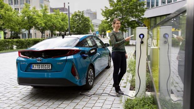 Junge Frau lädt Hybridauto mit ADAC Ladekarte an Ladesäule