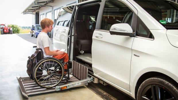 Rollstuhlfahrer steigt selbständig in ein umgebautes Auto ein mittels Hebebühne und Joystick