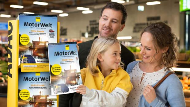 Junges Mädchen halt die neue ADAC Motorwelt Premium in ihren Händen, als sie mit ihren Eltern im Supermarkt ist