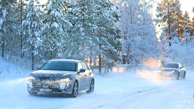 Zwei Erlkönige fahren auf einer verschneiten Strasse an einem verschneiten Wald vorbei