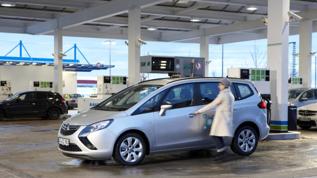 Eine Frau mit ihrem Auto beim tanken an der Tankstelle