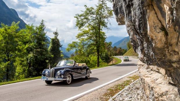 Ein Oldtimer vor einer Felswand beim ADAC Trentino Klassik