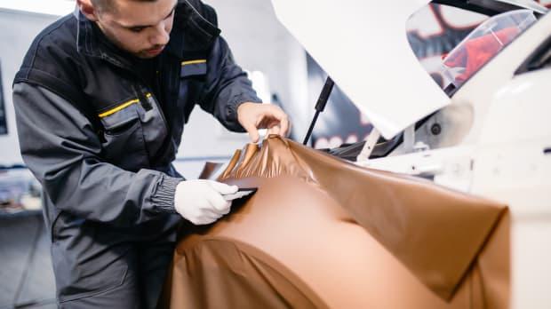 Ein Werkstattmitarbeiter foliert ein weisses Auto professionell mit bronzefarbener Folie