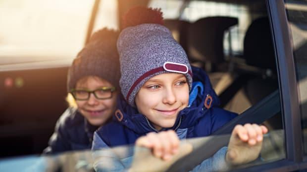 Zwei Kinder sitzen mit Winterjacke und Mütze im Auto am offenen Fenster