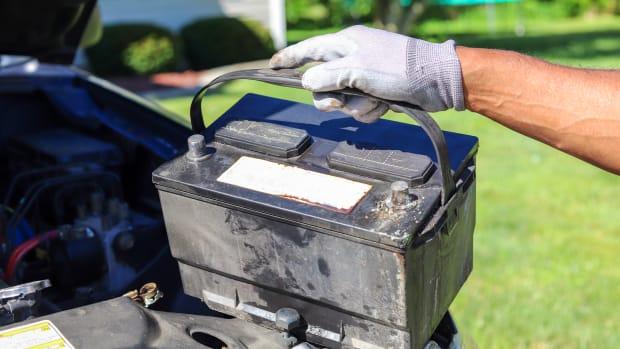 Mann entnimmt Batterie aus dem Auto