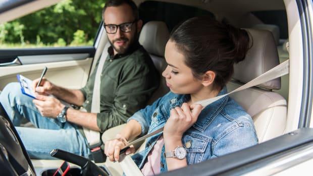 Frau und Prüfer sitzen während der Fahrprüfung im Auto