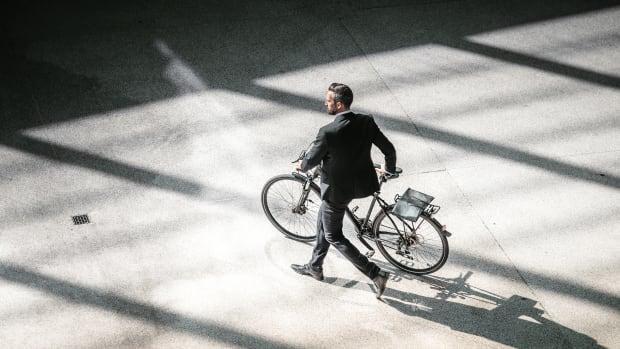 Ein Mann im Anzug schiebt sein Fahrrad, aus der Vogelperspektive aufgenommen.