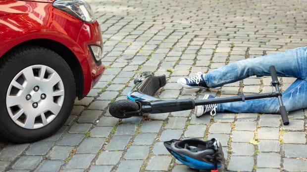 Ein E-Scooter-Fahrer liegt vor einem Auto auf der Strasse