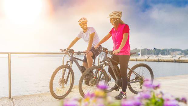 Zwei Radfahrer fahren an einem See vorbei